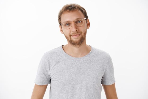 Uroczy przyjazny i przystojny mężczyzna europejczyk z brodą w okularach i szarej koszulce uśmiechnięty radośnie z zrelaksowaną i pełną ulgi miną słuchający pytania klienta nad białą ścianą