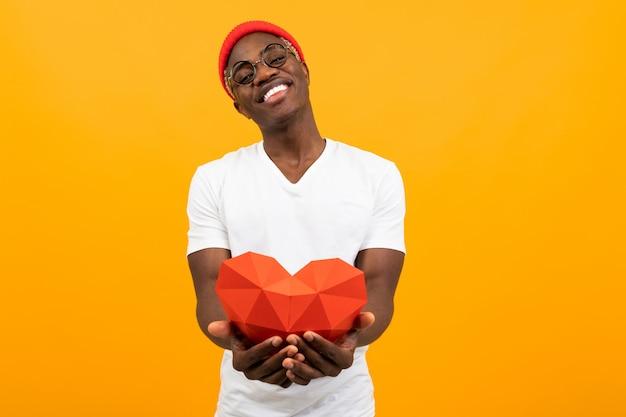 Uroczy przystojny afrykański mężczyzna z pięknym uśmiechem w białej koszulce wyciąga czerwone serce 3d wykonane z papieru na walentynki na żółtym