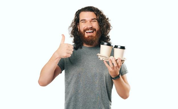 Uroczy przystojny brodaty mężczyzna pokazując kciuk do góry i trzymający dwie filiżanki kawy w podróży