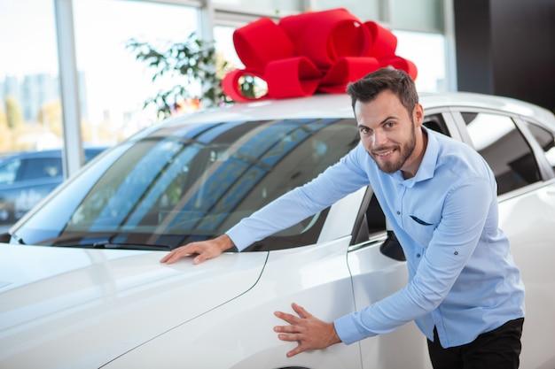 Uroczy przystojny mężczyzna uśmiecha się do kamery, dotykając pięknego nowego samochodu z czerwoną kokardą na dachu w salonie