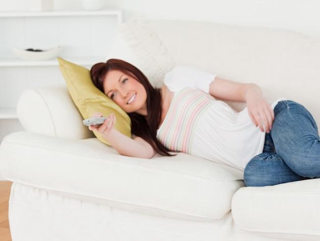 Uroczy rudowłosa kobieta oglądania telewizji, leżąc na kanapie