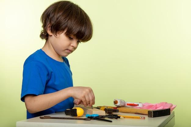 Uroczy śliczny chłopiec pracuje z narzędziami w niebieskiej koszulce i bieli