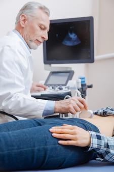 Uroczy spokojny, wykwalifikowany lekarz pracujący w szpitalu, wykonujący badanie ultradźwiękowe jamy brzusznej i ultrasonograf
