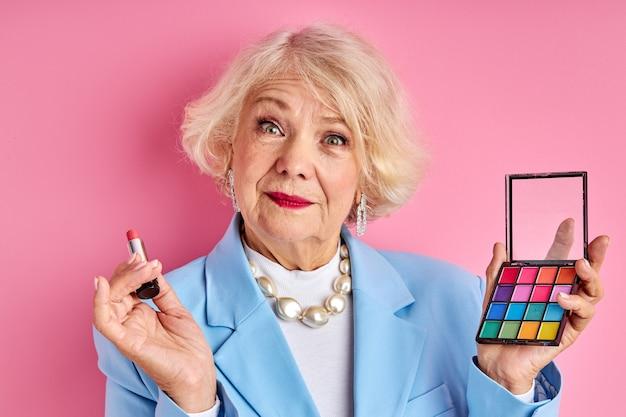 Uroczy starszy pani robi makijaż na białym tle w studio na różowo