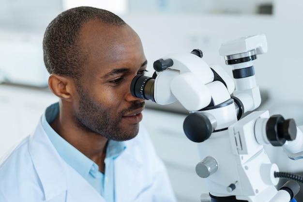 Uroczy, sympatyczny młody dentysta przy pracy pod mikroskopem, sprawdzający mikropęknięcia w zębach pacjentów
