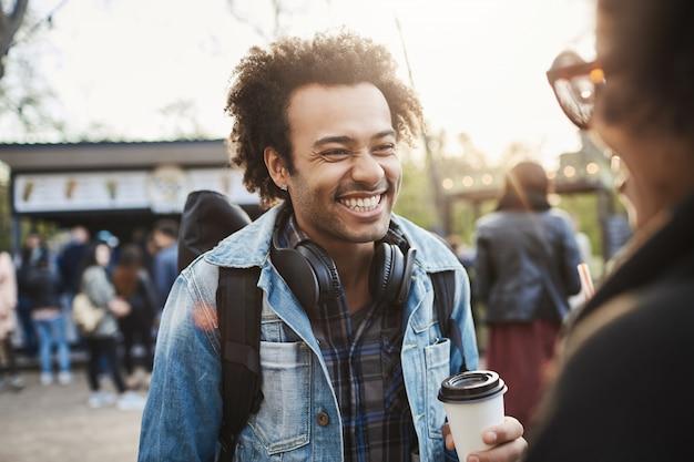 Uroczy szczęśliwy chłopak z fryzurą afro, uśmiechając się i śmiejąc się podczas rozmowy z dziewczyną i picia kawy w parku.