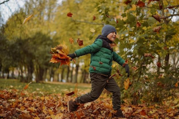 Uroczy sześciolatek z rasy kaukaskiej bawi się w parku biegając i rzucając suche liście w powietrze