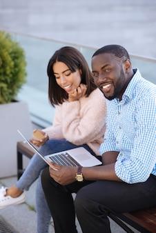 Uroczy, uprzejmy i zalotny facet, który pyta znajomych o radę podczas zakupów w internecie i płatności kartą kredytową
