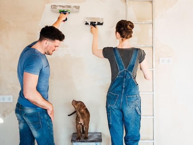 Uroczy, uroczy szczeniaczek w kolorze brązowym i małżeństwo podczas napraw.