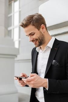 Uroczy uśmiechnięty młody biznesmen w garniturze stojący w mieście, korzystający z telefonu komórkowego