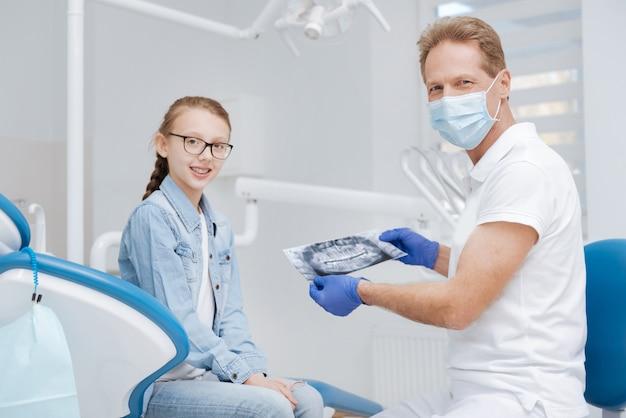 Uroczy wspaniały doświadczony lekarz prowadzący spotkanie konsultacyjne i studiujący dziewczyny proszą o przepisanie jej odpowiedniego leczenia