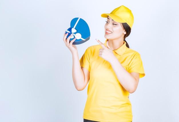 Uroczy współpracownik trzymający pudełko prezentowe i wskazujący na nim palec