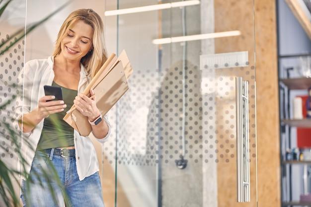 Uroczy żeński pracownik biurowy wysyła wiadomość sms na smartfonie i uśmiecha się trzymając dokumenty