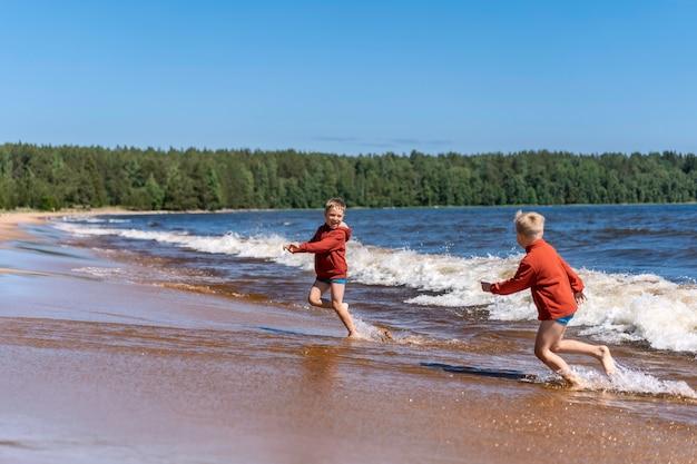 Uroczych kaukaskich chłopców w czerwonych bluzach z kapturem i niebieskich majtkach biegnących przed falami w jeziorze ładoga