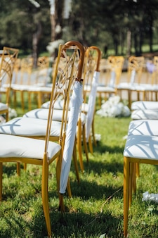 Uroczysta ceremonia ślubna. wiszący parasol na pustym krześle.