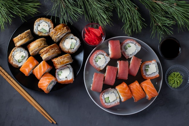 Uroczysta kolacja wigilijna z sushi z łososiem, tuńczykiem i węgorzem z serem philadelphia. widok z góry na ciemnym tle