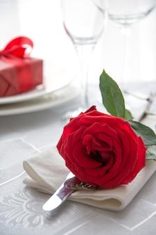 Uroczysta lub romantyczna kolacja z czerwoną różą i prezentem. romantyczne zaproszenie