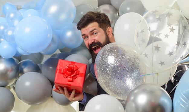 Uroczyste wydarzenie lub przyjęcie urodzinowe z okazji urodzin facet trzyma balony z helem i pudełko na prezent przystojny mężczyzna