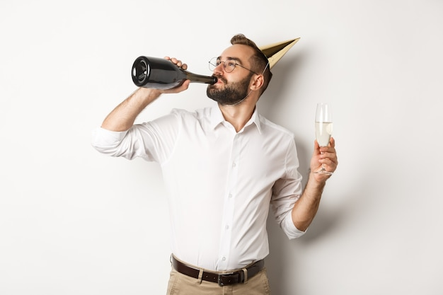 Uroczystość i święta. mężczyzna pije chamapgne z butelki na przyjęcie urodzinowe, stojąc na białym tle.
