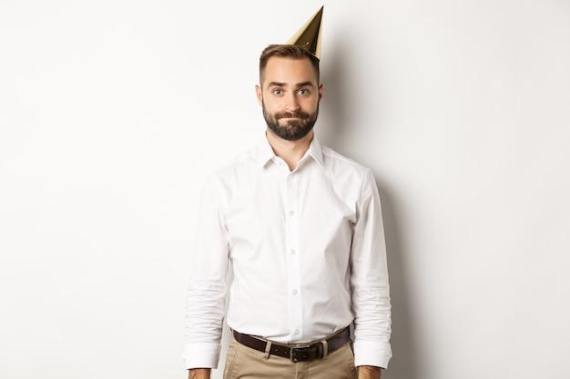 Uroczystość i święta. ponury facet w urodzinowej czapce stoi niezgrabnie na białym tle i nie czuje się rozbawiony.