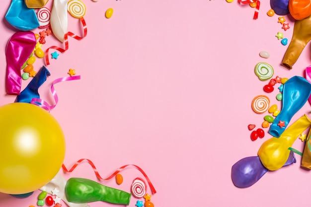 Uroczystość leżała płasko. cukierki z kolorowymi imprezowymi przedmiotami na różowym tle.