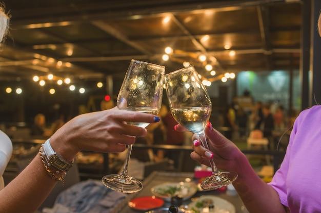 Uroczystość. ludzie trzymający kieliszki białego wina wznosząc toast.