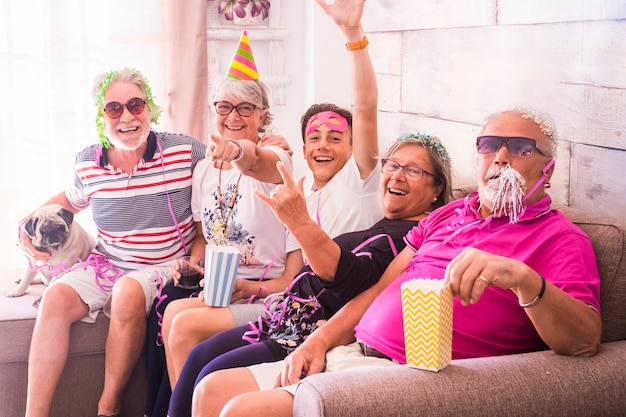 Uroczystości karnawałowe, takie jak urodziny lub sylwester, dla rodziny z mieszanymi pokoleniami od opld do nastolatków. pies mops też wszyscy bawią się razem w domu