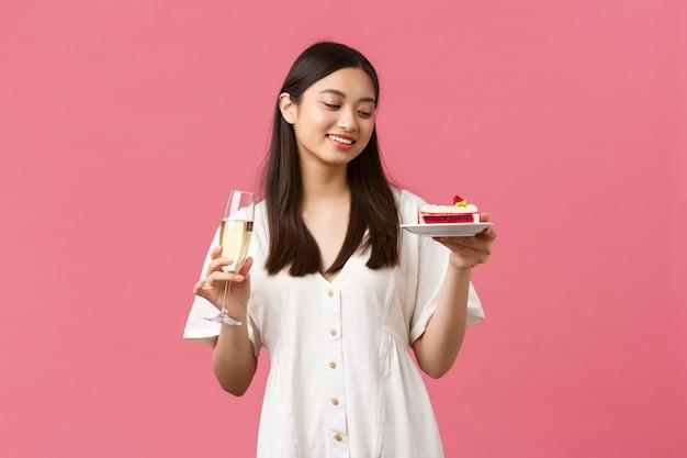 Uroczystości, święta i zabawy koncepcja. marzycielska piękna kobieta świętująca urodziny kieliszkiem szampana i tortem urodzinowym, uśmiechnięta beztrosko przy deserze, stojąca na różowym tle.