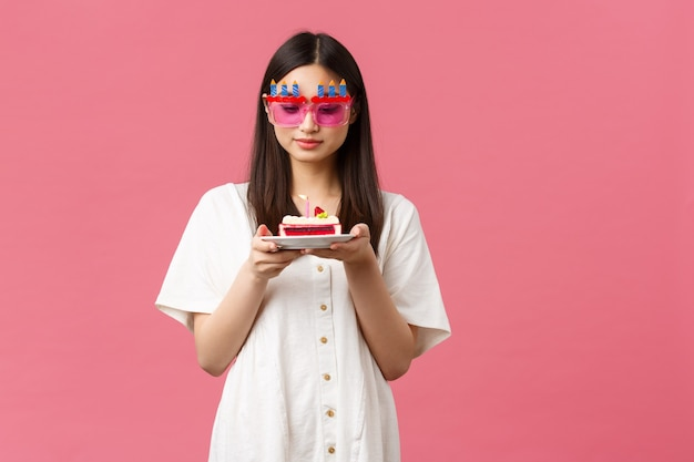 Uroczystości, święta i zabawy koncepcja. marzycielska śliczna urodzinowa dziewczyna w śmiesznych okularach przeciwsłonecznych, trzymająca tort urodzinowy i patrząc na świecę zamyślona, życząc, stojąc na różowym tle.