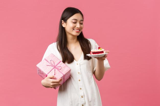 Uroczystości, święta i zabawy koncepcja. marzycielska szczęśliwa ładna urodzinowa dziewczyna w białej sukni, uśmiechnięta i odwracająca wzrok jako otrzymująca prezent, jedząca tort urodzinowy, różowe tło