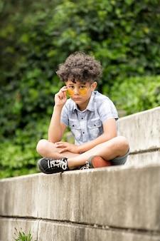 Uroczysty mały chłopiec w żółtych okularach przeciwsłonecznych