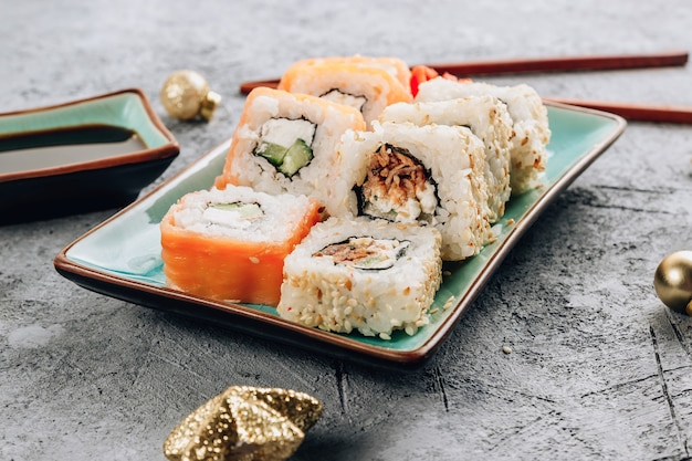 Uroczysty obiad bożonarodzeniowy z zestawem sushi i świąteczną dekoracją na betonowym tle. sylwestrowa impreza.
