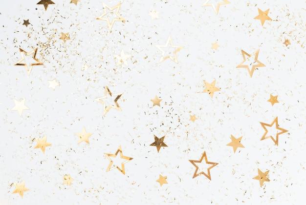 Uroczysty pastelowe tło. boże narodzenie gwiazdki i błyszczący brokat, konfetti na pastelowym tle. boże narodzenie tło, leżał płasko.