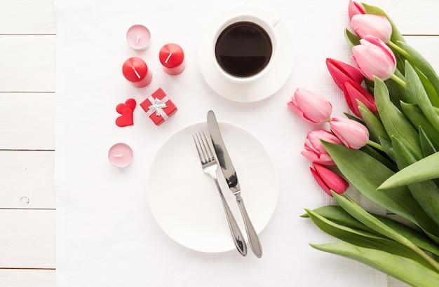 Uroczysty romantyczny stół ze srebrnymi sztućcami i bukietem świeżych różowych tulipanów.