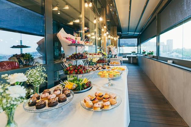Uroczysty stół bufetowy z pysznymi deserami w różnych kolorach na ceremonii ślubnej