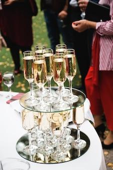Uroczysty stół w formie bufetu. na stole są kieliszki szampana.