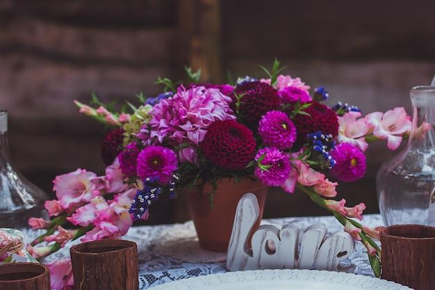 Uroczysty stół zdobią kompozycje kwiatowe. oryginalna ślubna dekoracja kwiatowa na weselnym stole