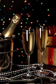 Uroczysty szampan z kieliszkiem na lampkach świątecznych