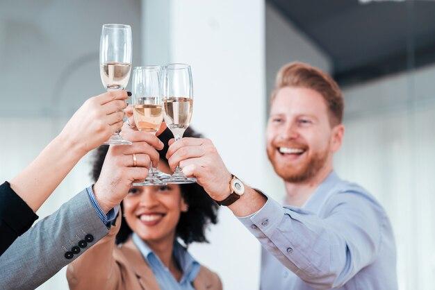 Uroczysty toast. ludzie biznesu szczęk szklanki w biurze.