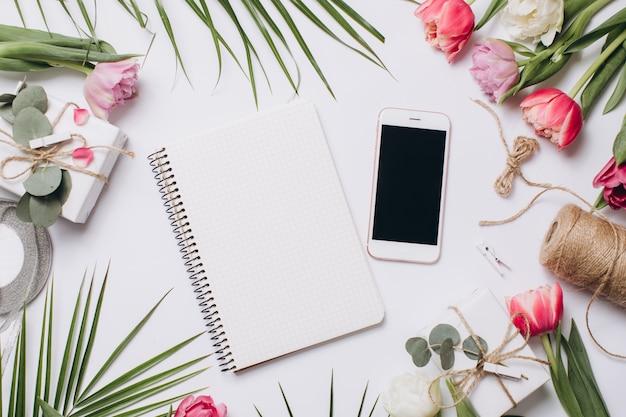 Uroczysty układ: pudełka z prezentami, wstążkami, notatnikiem, telefonem komórkowym i tulipanami