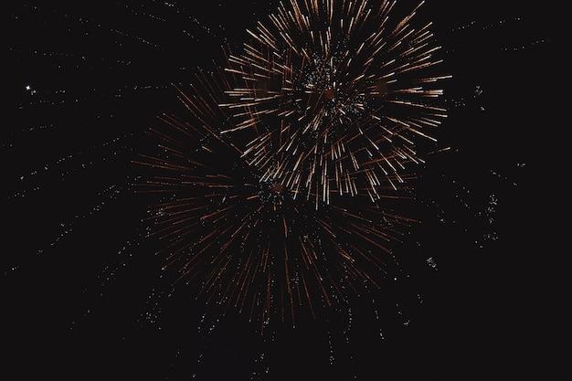 Uroczysty wielobarwny pozdrawiać na tle ciemnego nocnego nieba. pozdrów od pirotechniki.