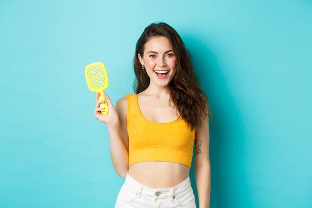Uroda i kosmetyki. uśmiechnięta kobieta ze świecącą kręconą fryzurą, pokazująca szczotkę bez kosmyków, dbająca o zdrowie, stojąca na niebieskim tle.
