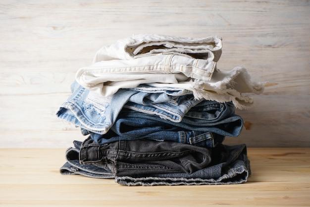 Uroda i moda, koncepcja odzieży - stos dżinsów na podłoże drewniane