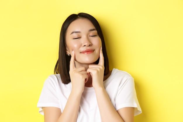 Uroda i pielęgnacja skóry. zbliżenie młodej azjatyckiej kobiety o krótkich ciemnych włosach, zdrowej świecącej skórze, uśmiechniętej i dotykającej dołeczkach na policzkach, stojącej na żółto.
