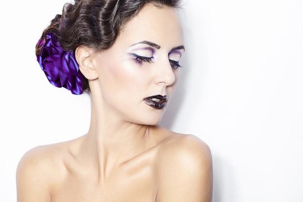Uroda i zdrowie, kosmetyki i makijaż. portret mody kobiety model z jaskrawym purpurowym makeup, kędzierzawa fryzura na jasnym białym tle.