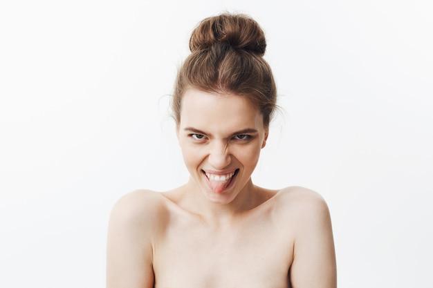 Uroda i zdrowie urocza śmieszna europejska chuda kobieta z ciemnymi włosami w kokowej fryzurze jest naga, mruga, uśmiecha się, pokazuje język, robi śmieszne i głupie miny.