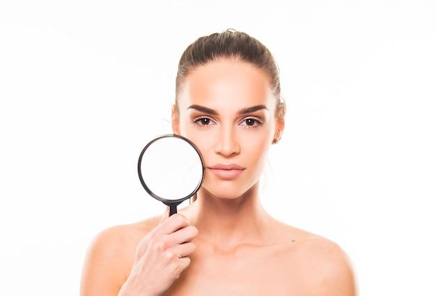 Uroda, koncepcja produktu do pielęgnacji skóry. portret dziewczynki trzyma lupę na skórze na twarzy.