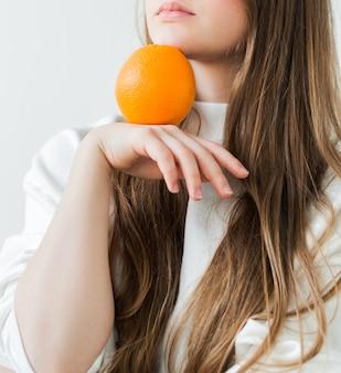 Uroda, kosmetyki naturalne, pojęcie zdrowia. dziewczyna o spokojnych emocjach w białej koszulce trzyma w rękach pomarańczę. zdjęcie pionowe