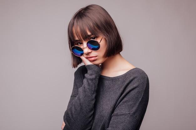 Uroda moda brunetka dziewczyna nosi stylowe okulary przeciwsłoneczne. portret seksowny kobiety z odizolowanych na szarej ścianie.