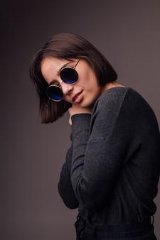 Uroda moda brunetki młoda dziewczyna model na sobie stylowe okulary przeciwsłoneczne izolowany na szaro. blogerka modowa